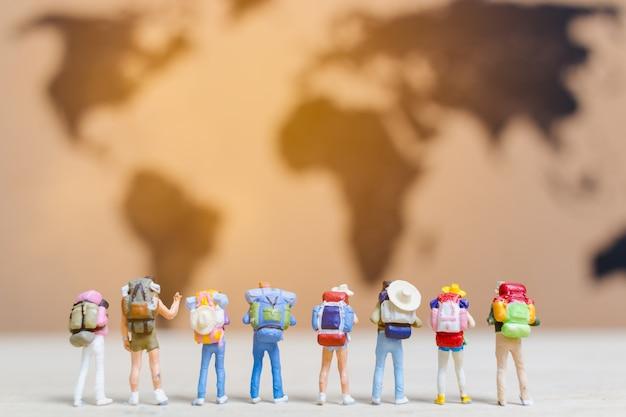 Viaggiatori di persone in miniatura che camminano sulla mappa del mondo