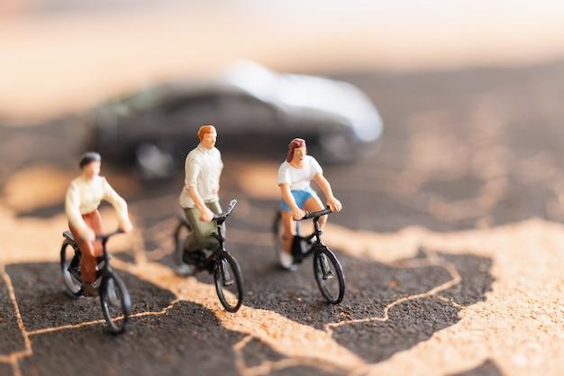 Viaggiatori di persone in miniatura con la bicicletta