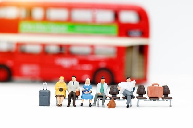 Persone in miniatura con bagaglio in attesa del bus
