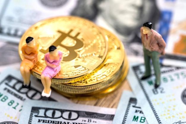 Persone in miniatura con bitcoin e dollari