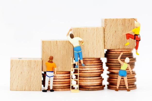 Persone in miniatura con pila di monete e scatola di legno.