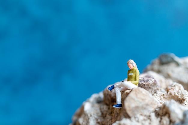 Persone in miniatura donna che indossa le cuffie e ascolta la musica sullo smartphone seduto sulla roccia