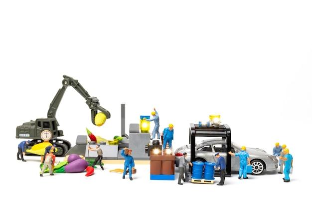 Le persone in miniatura lavorano alla stazione di pompaggio del carburante biologico con veicoli in un ambiente di aria pulita senza gas serra e co2, concetto di sistema di biocarburante