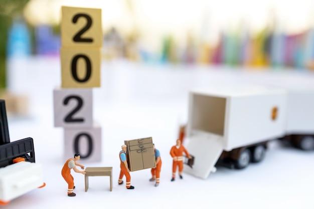 Persone in miniatura: scatola di caricamento del lavoratore e monete per il contenitore del camion. concetto di servizio di spedizione e consegna online.