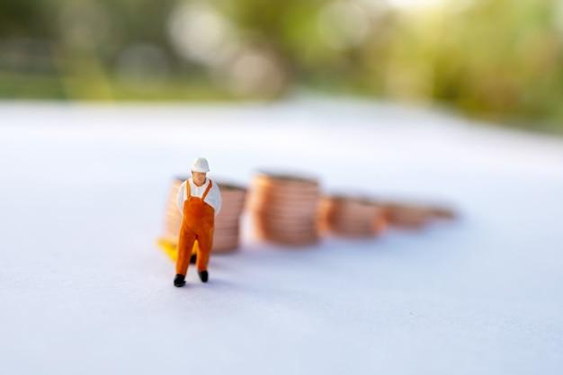 Persone in miniatura: lavoratore che carica monete nel contenitore del camion. concetto di servizio di spedizione e consegna online.