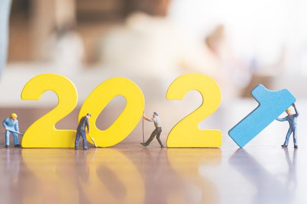 Persone in miniatura: la squadra di lavoratori costruisce il numero di legno 2021, concetto di felice anno nuovo