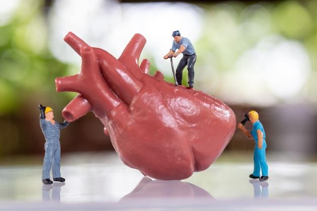 Persone in miniatura il team di lavoratori esamina il cuore ascolta un battito cardiaco e fa una diagnosi.trattamento e controllo del concetto di cuore