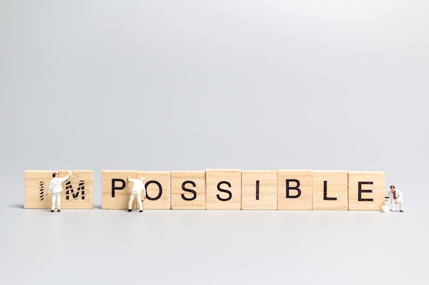 Squadra di lavoratori di persone in miniatura sulla parola impossibile in lettere dell'alfabeto in legno con il prefisso un cancellato, lasciando la parola possibile