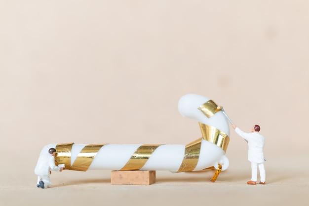 Persone in miniatura, squadra di lavoratori che dipinge una decorazione di natale, natale e un concetto di felice anno nuovo.
