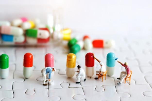 Persone in miniatura: gruppo di operai che dipinge a pennello capsule medicinali. concetto di assistenza sanitaria, medica e aziendale.