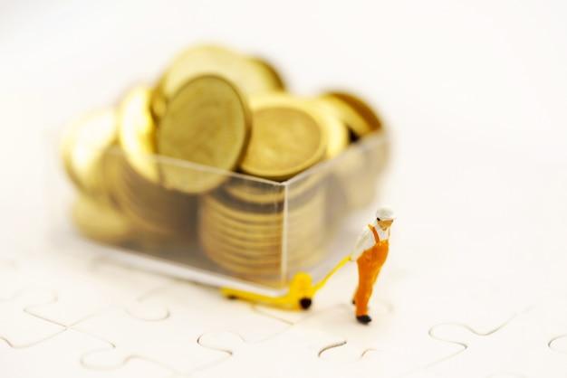 Persone in miniatura: i lavoratori trasportano monete con denaro. concetto di finanza e investimenti.