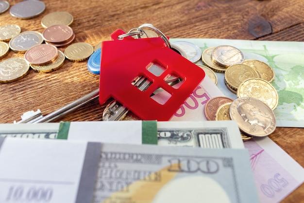 Chiavi di casa rossa in miniatura sulle banconote e monete