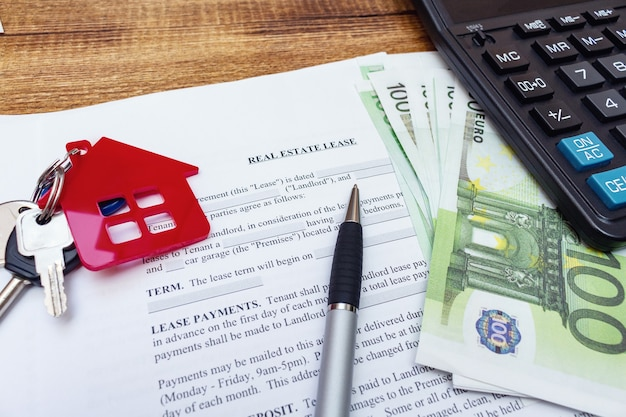 Chiavi della casa rossa in miniatura con banconote