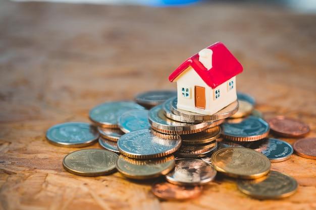 Casa rossa in miniatura sulla pila di monete utilizzando come proprietà e concetto finanziario aziendale