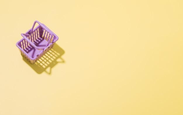 Cestino della spesa in miniatura in un supermercato su sfondo giallo. concetto di shopping minimalista con copia spazio