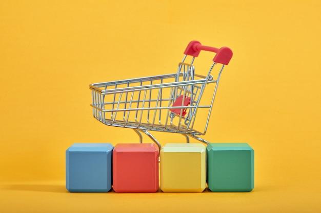 Un carrello della spesa in miniatura e blocchi di legno con le diciture vendita, isolato su sfondo menta.