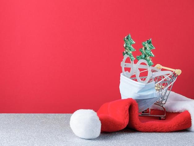 Carrello della spesa in miniatura coperto con una mascherina chirurgica e decorazioni natalizie isolate su sfondo rosso e argento con spazio di copia