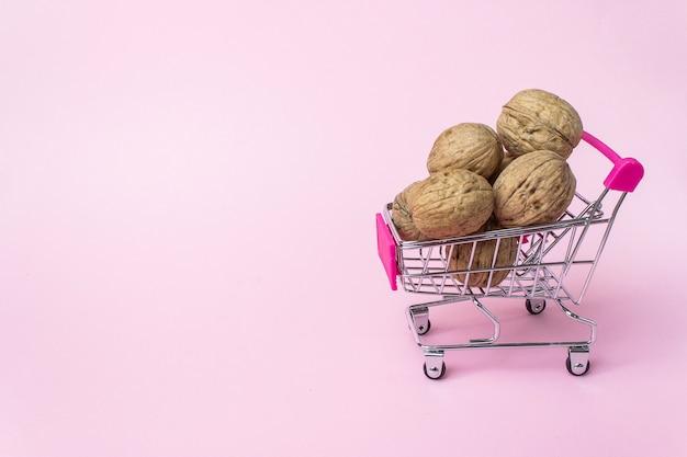 Carrello per supermercati in miniatura con noce su sfondo rosa.. saltellando, acquisti, supermercato,