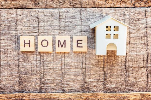 Casa giocattolo in miniatura con scritta home lettere parola su sfondo di legno