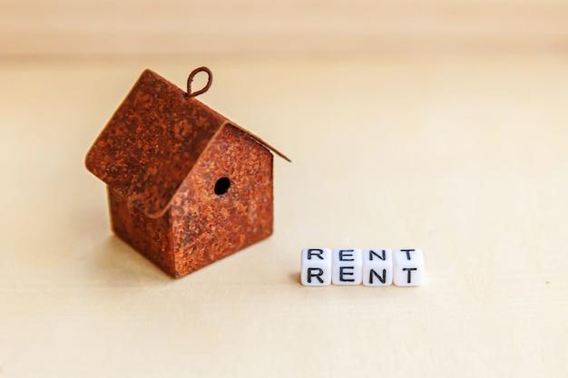 Giocattolo in miniatura casa modello con iscrizione affitto lettere parola su sfondo di legno