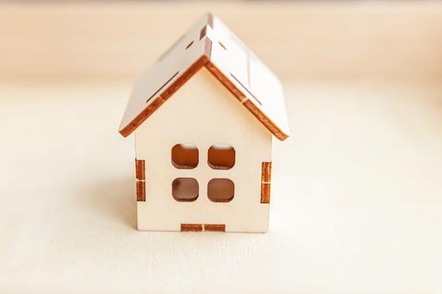 Casa modello giocattolo in miniatura su sfondo in legno. eco villaggio, sfondo ambientale astratto