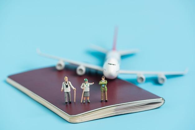Viaggiatore in miniatura e modello di aereo sul libro passaporto