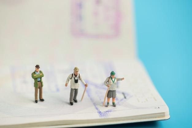 Viaggiatore in miniatura sul libro del passaporto