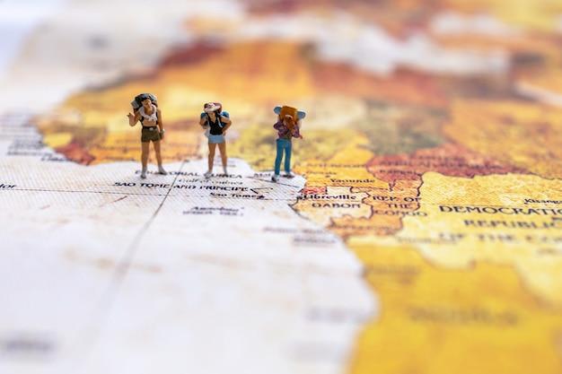 Viaggiatore in miniatura con uno zaino in piedi sulla mappa del mondo. concetto di viaggio.