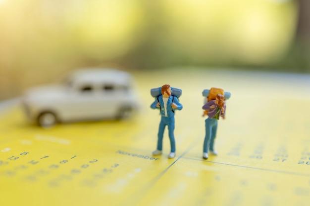 Viaggiatori in miniatura con uno zaino in piedi sul calendario, viaggi e concetto di vacanza.