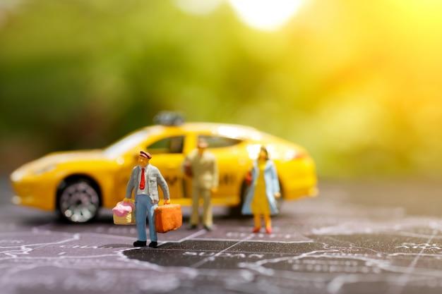 Miniatura del viaggiatore con il viaggiatore con zaino e sacco a pelo sulla mappa con il taxi
