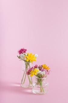 Vasi in miniatura con fiori di campo su uno sfondo rosa con copia spazio per congratulazioni per l'8 marzo, pasqua, festa della mamma