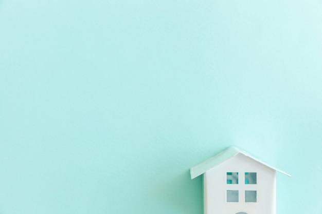 Casa bianca in miniatura del giocattolo su fondo pastello blu