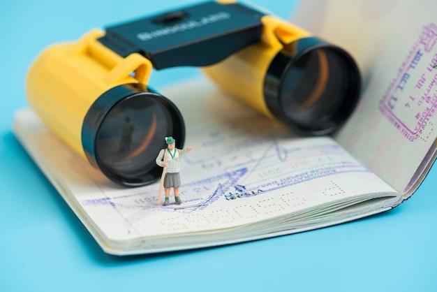 Viaggiatore in miniatura delle donne e binocolo sul libro del passaporto
