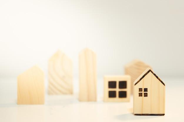 Casa in legno in miniatura sul tavolo di legno. concetto finanziario del bene immobile di ipoteca della casa e di investimento immobiliare.