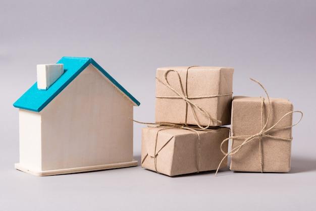 Casa in legno in miniatura, simbolo, con scatole, consegna a domicilio