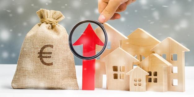 Casa in legno in miniatura e freccia alta con fiocchi di neve. il concetto di forte domanda abitativa.