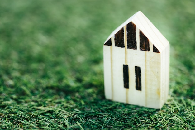 Casa bianca di legno miniatura su erba verde. concetto finanziario del bene immobile di ipoteca della casa e di investimento immobiliare.
