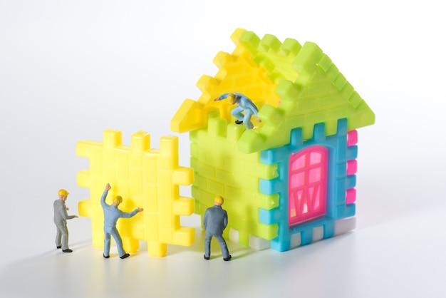 Squadra di persone in miniatura della costruzione della casa su sfondo bianco