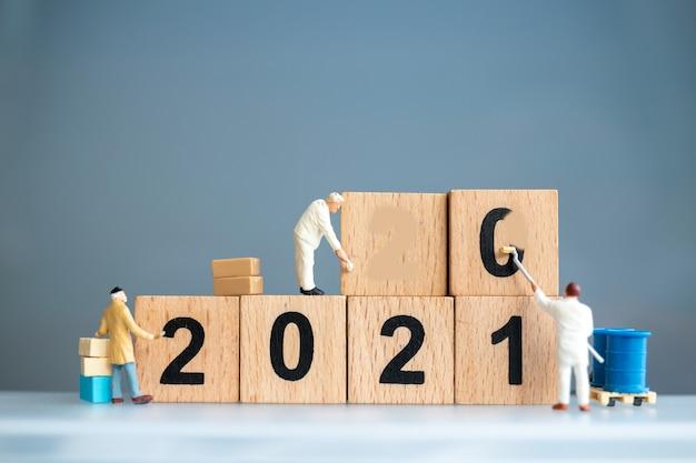 La squadra di lavoratori in miniatura ha dipinto il numero 2021 e rimuove il numero 2020, concetto di felice anno nuovo