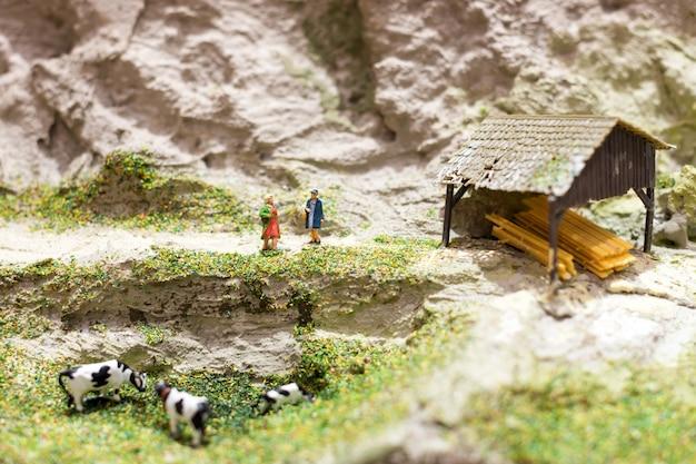 Mondo in miniatura con due donne in piedi su un sentiero di montagna e parlando vicino al pascolo delle mucche