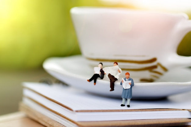 Miniature persone sedute su una tazza di caffè