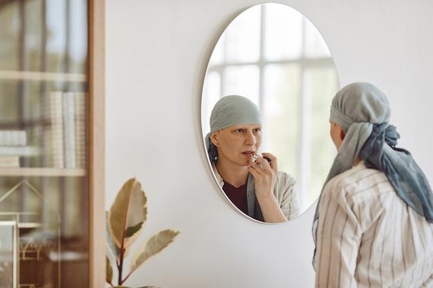 Ritratto di vista posteriore minima di donna calva matura che mette il trucco e il rossetto mentre si guarda nello specchio a casa, abbracciando la bellezza, l'alopecia e la consapevolezza del cancro, lo spazio della copia