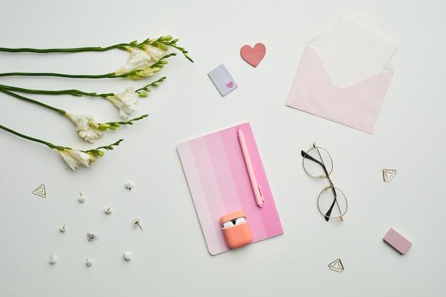 La minima composizione di sfondo di stazionario a tema femminile, accessori e occhiali da vista sul tavolo bianco con decorazioni floreali,