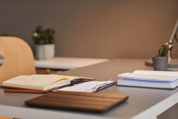 Immagine di sfondo minima del libro aperto alla scrivania sul posto di lavoro illuminata da luci calde, spazio di copia