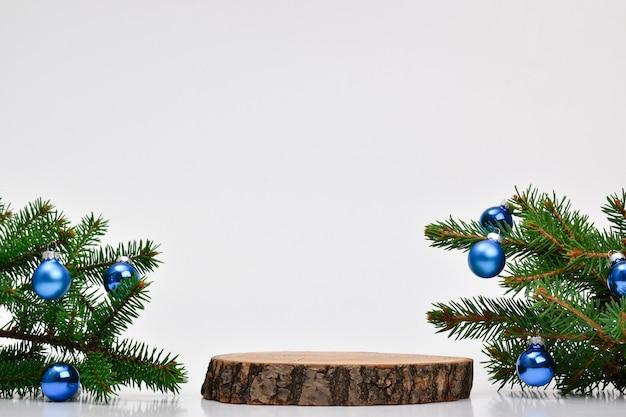 Minimo. sfondo di natale con un podio per la presentazione di un prodotto. il piedistallo è realizzato in legno naturale. felice anno nuovo e buon natale.