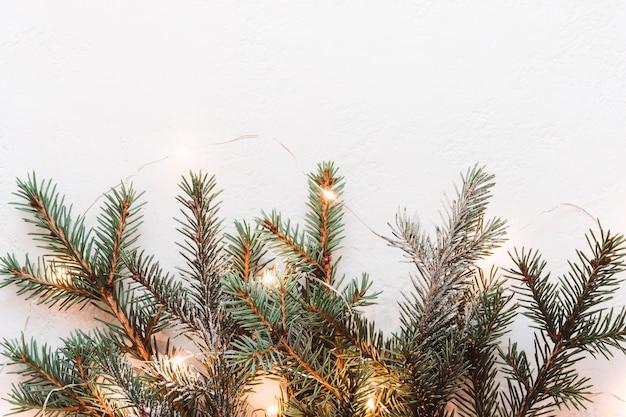 Decoro natalizio minimale fatto di rami di abete e ghirlanda di luci dorate.
