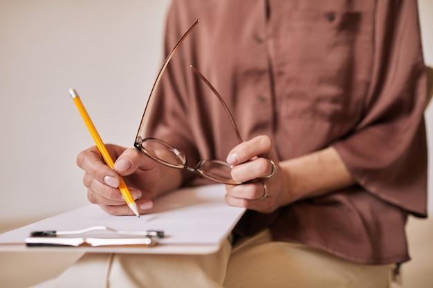 Primo piano minimo di psicologa femminile irriconoscibile che scrive negli appunti durante la sessione di terapia nel gruppo di supporto, copia spazio