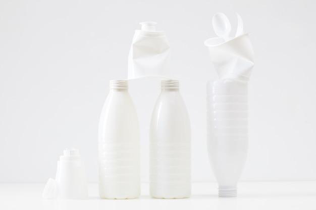 Composizione minima di bottiglie e oggetti di plastica bianca, raccolta differenziata e concetto di riciclaggio