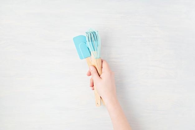 Composizione minima con womanhand che tiene gli utensili da cucina con lo spazio della copia. mangiare sano, cucina casalinga, ricette online, concetto di lezioni di internet. mockup, vista dall'alto, piatto laico