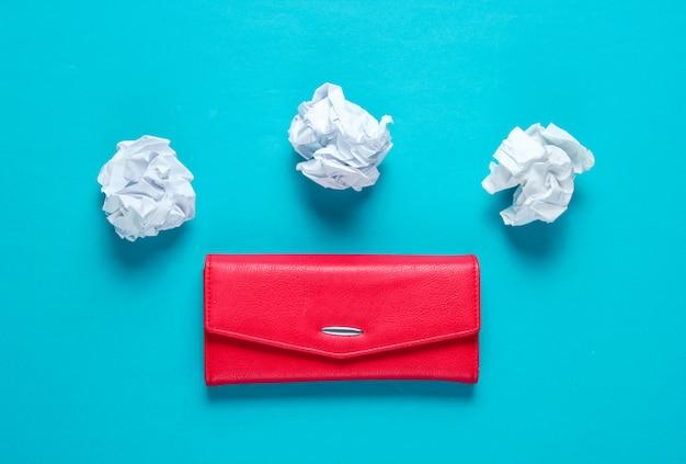 Concetto minimale. palle di carta stropicciata, portafoglio in pelle rossa sul tavolo blu